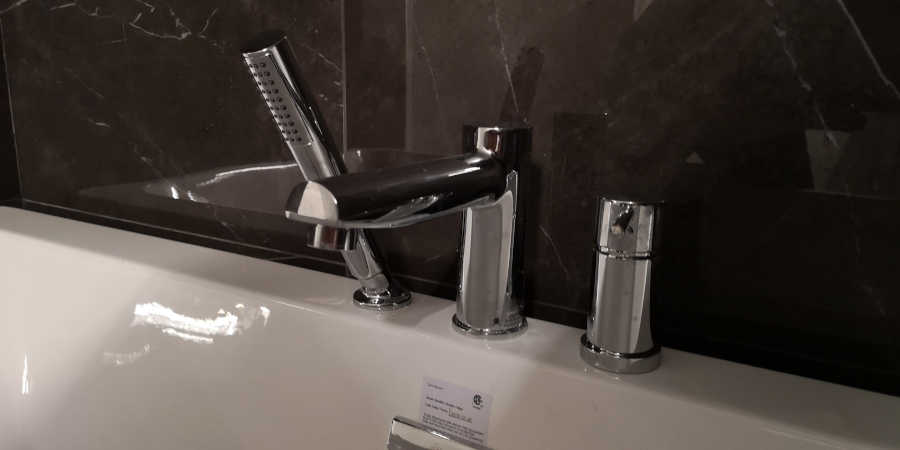 robinson light and bath faucet mounted on bathtub
