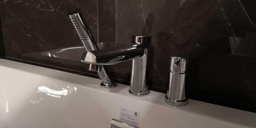 robinson light and bath faucet mounted on bathtub